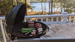 Photo of meat and veg on the grill, infront of lake.