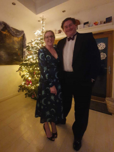 Alex and his wife in-front of a Christmas tree